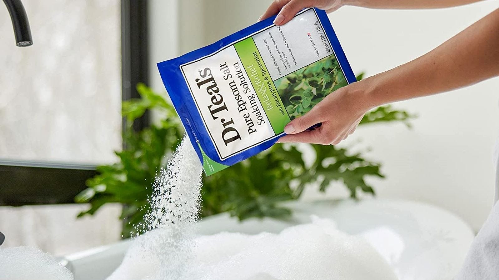 A woman pouring Dr Teals' Epsom Salts into a tub.