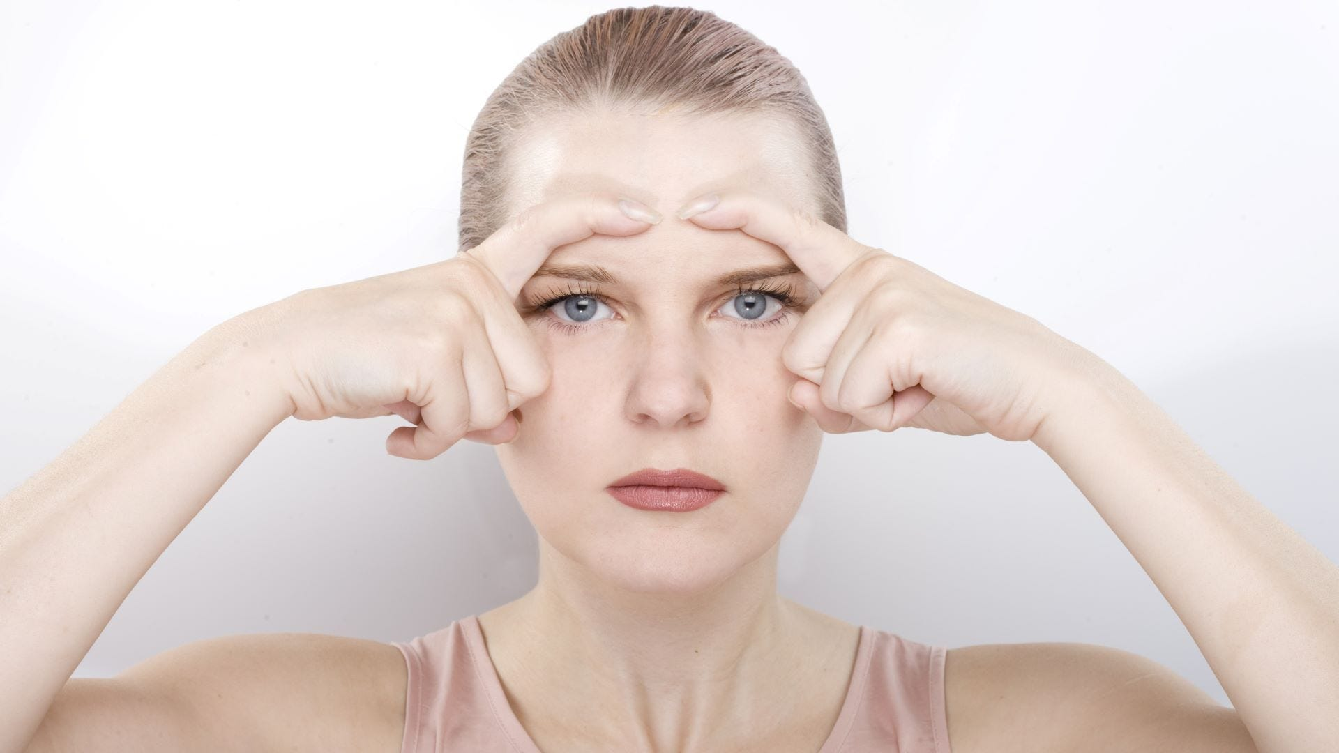 """A woman using the """"C' eye face yoga pose."""