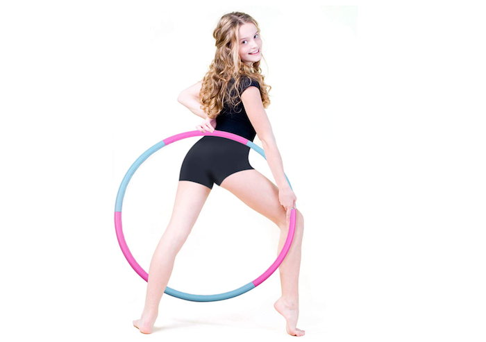 young girl posing with a blue and pink hula hoop