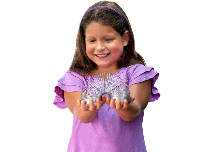 girl holding a metal Slinky in front of her.