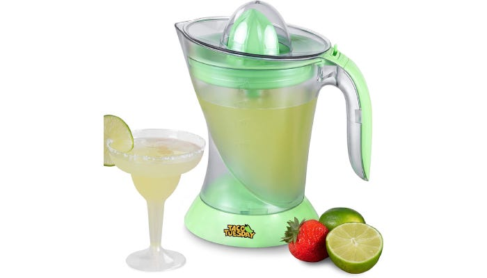 Tall pitcher filled with margarita drink. One prepared glass on left, lime and strawberry on right