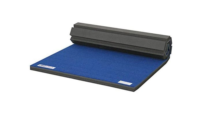 A blue gymnastics mat partially rolled up.