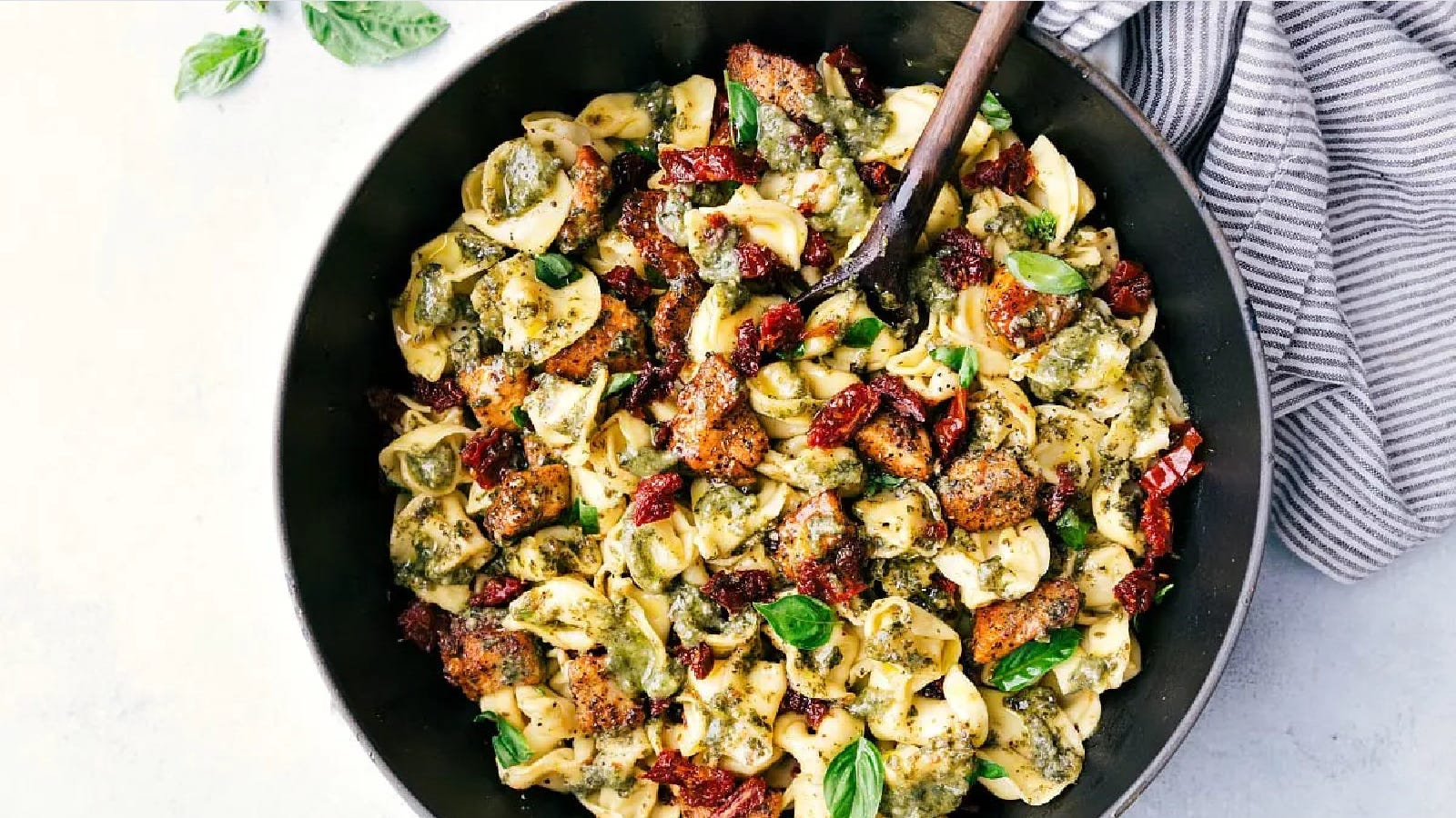 A large bowl filled with pesto chicken tortellini, accented with sundried tomatoes and fresh basil leaves.