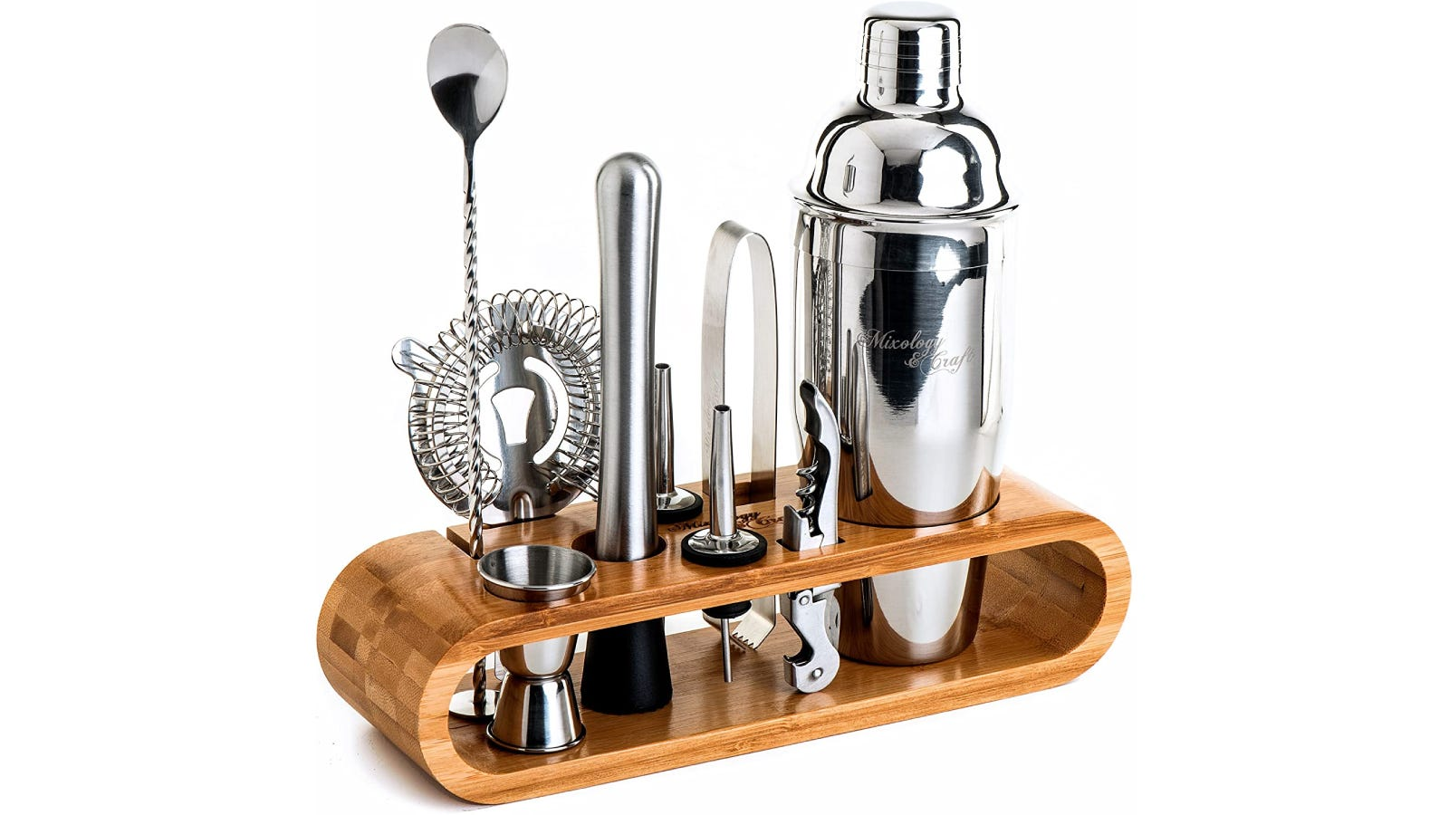 silver Parisian cocktail shaker in bamboo stand with tools that include spoon, jigger, strainer, and muddler