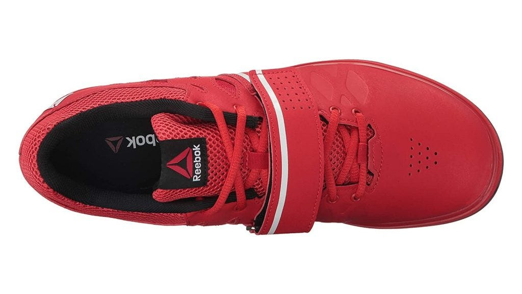 a red Reebok weightlifting shoe with a Velcro strap over the middle
