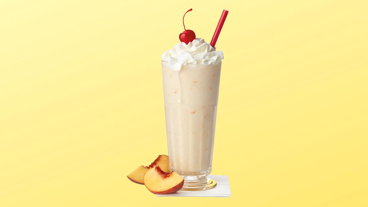 A Chick-fil-A peach milkshake next to some sliced peaches.