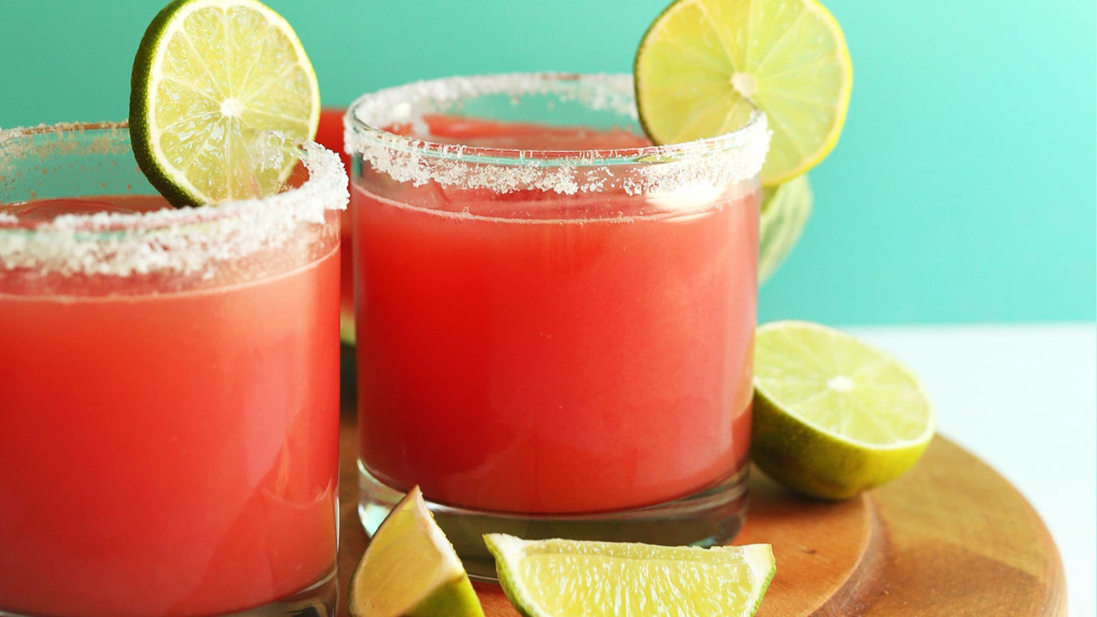 Two watermelon margaritas, with salted rims and lemon wheel garnishes.