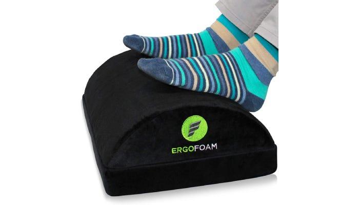 Feet in blue striped socks resting on a foam footrest