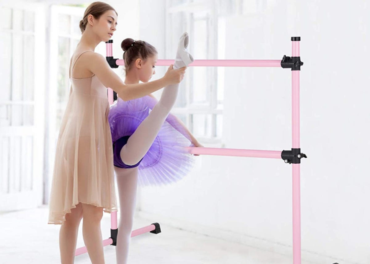 A woman helping younger girl in ballet dresses on barre.