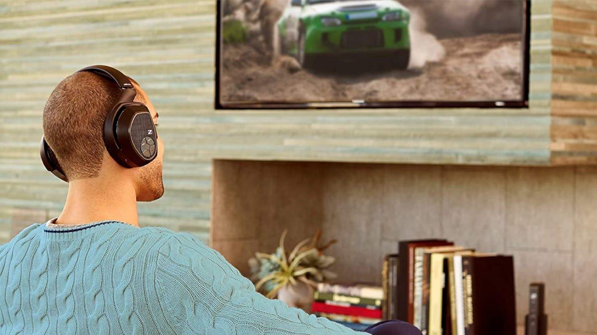 Man watching TV while using black Sennheiser wireless headphones