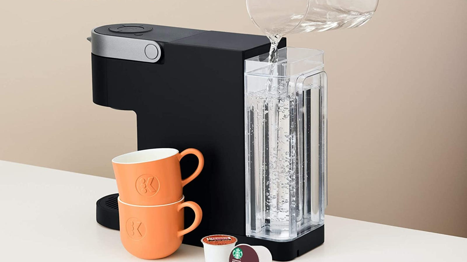 A fancy self serve Keurig coffee maker being refilled with water with two coffee cups next to the machine.