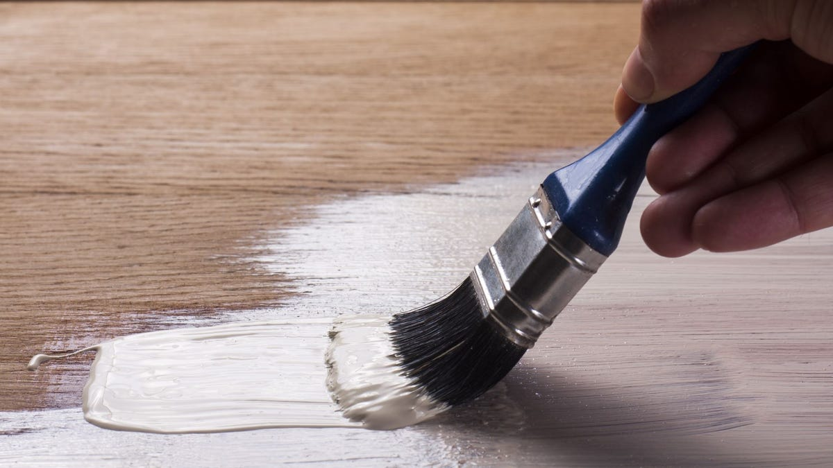 Someone painting a hardwood floor white.