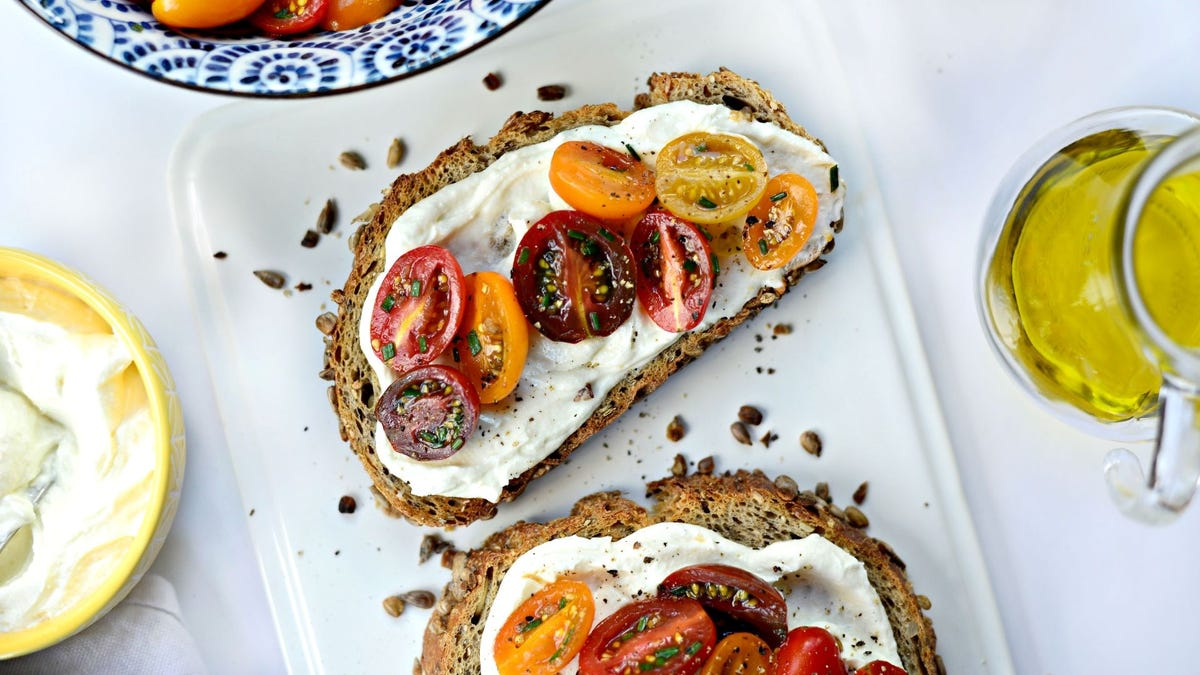 Two pieces of whipped feta toast topped with marinated tomatoes.