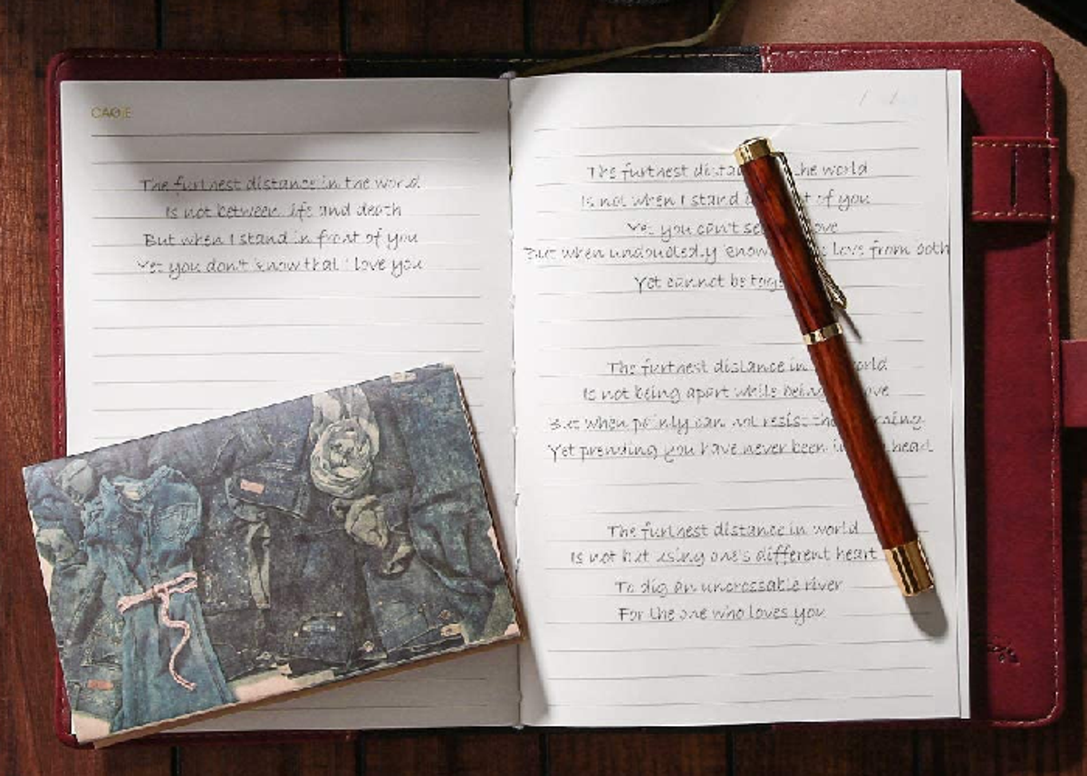 An open journal with writing on the pages and a pen and card on top of it