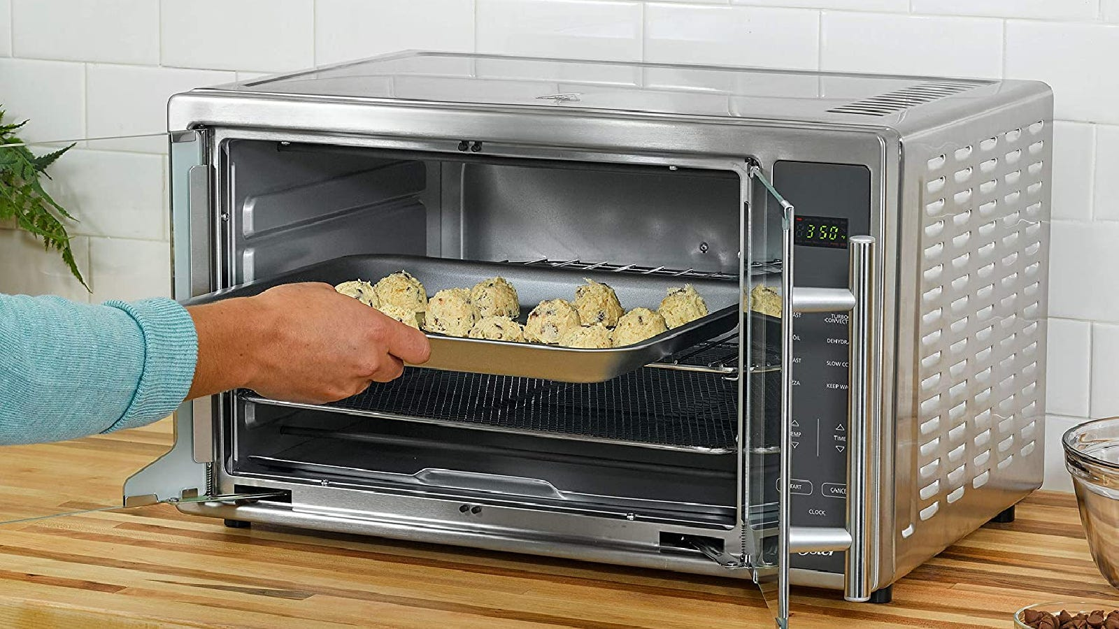 A person putting a tray of cookie dough inside a toaster oven.