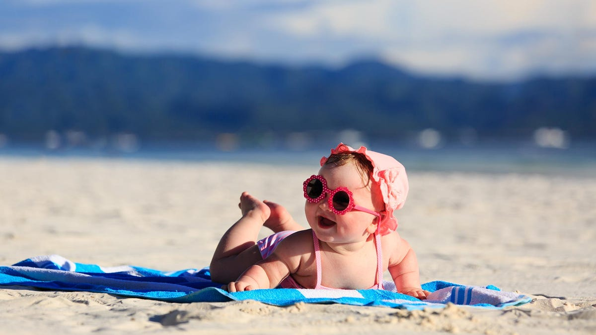 A baby playing at the beach, laying on a towel.