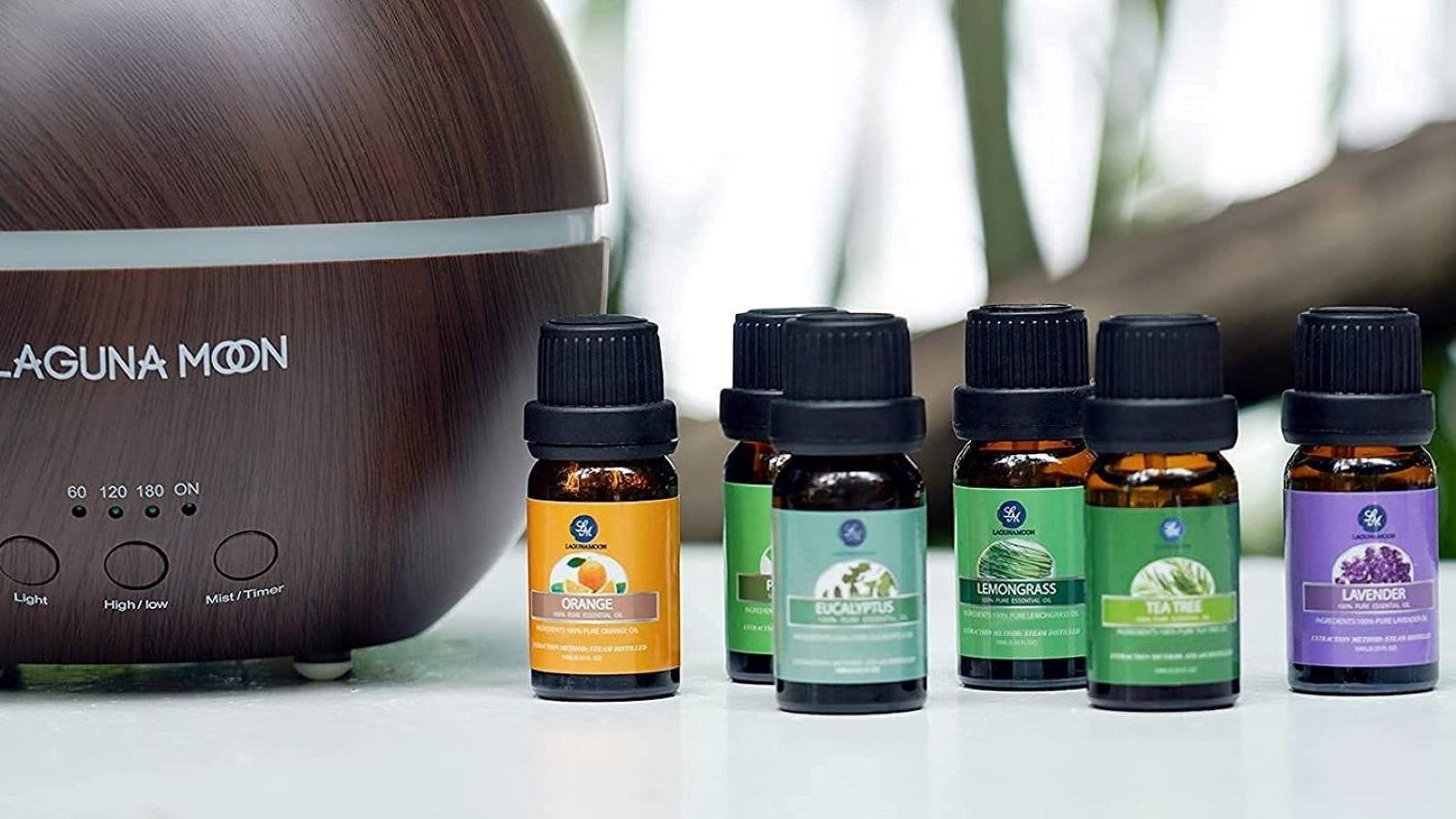 Six bottles of Laguna Moon Essential Oils next to the Laguna Moon diffuser.