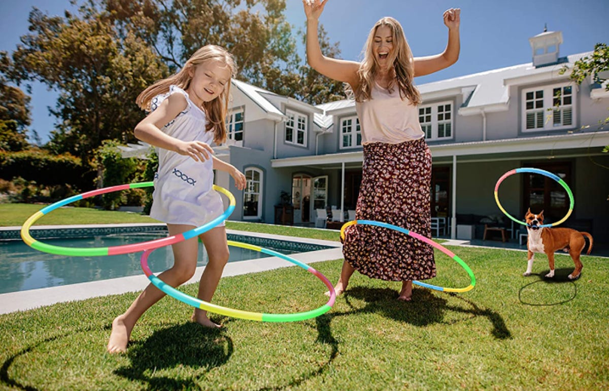 young girl, her mother, and a dog playing with hula hoops in their backyard