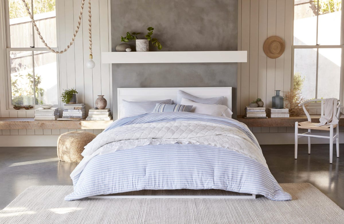 A bedroom featuring a blue and white striped comforter, faux plants, and ample pillows from Gap Home.