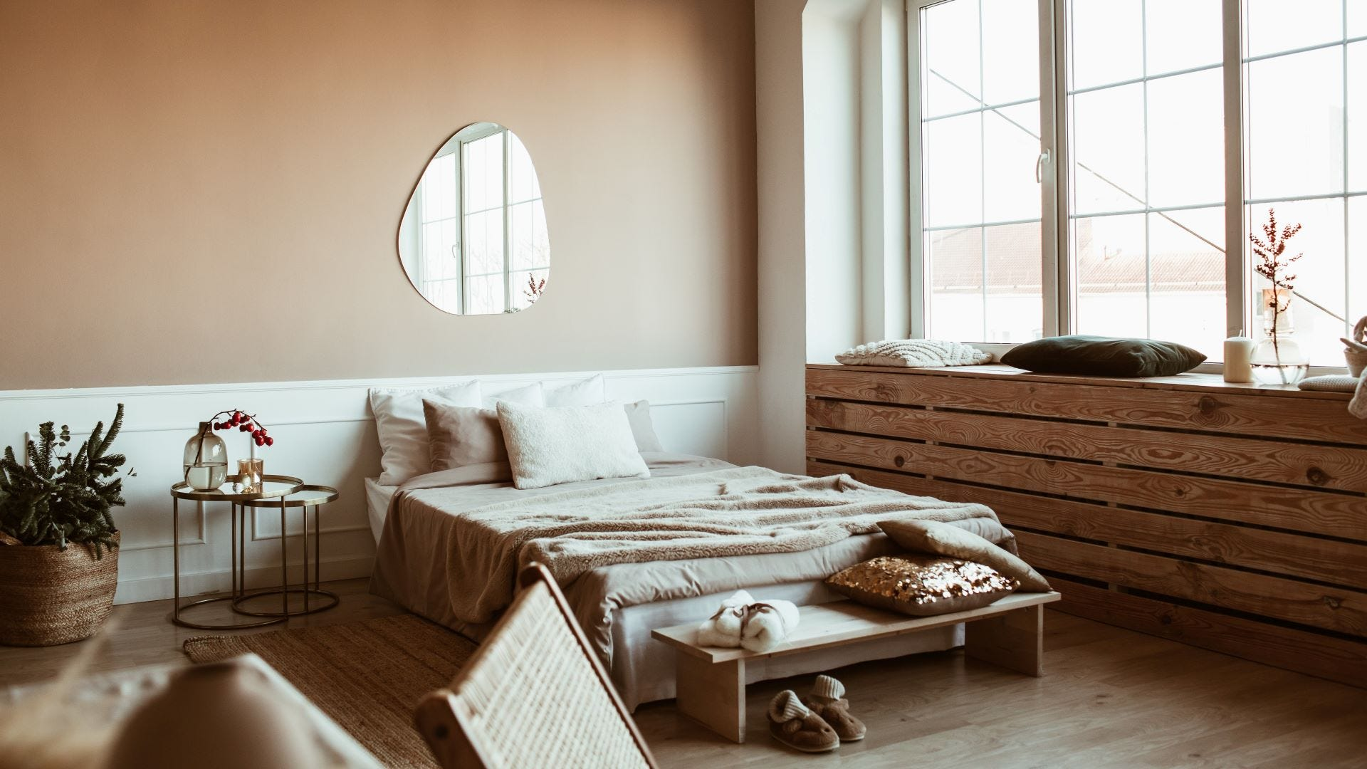 A blush and beige bedroom with wooden accents and plants.