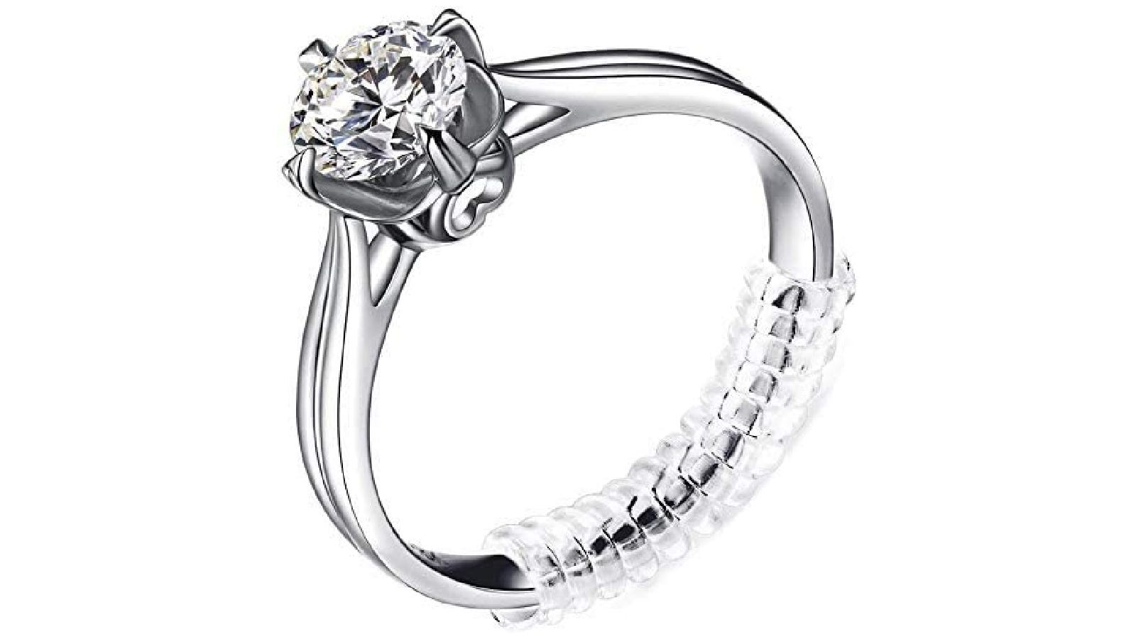 A silver diamond ring with a transparent ring adjuster wrapped around the ring base.