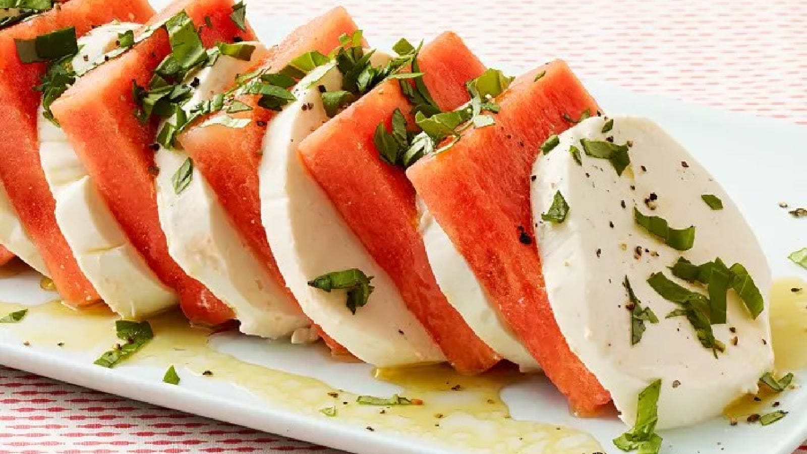 A serving plate with layered watermelon and fresh mozzarella caprese drizzled with a quick vinaigrette and garnished with chopped basil leaves.