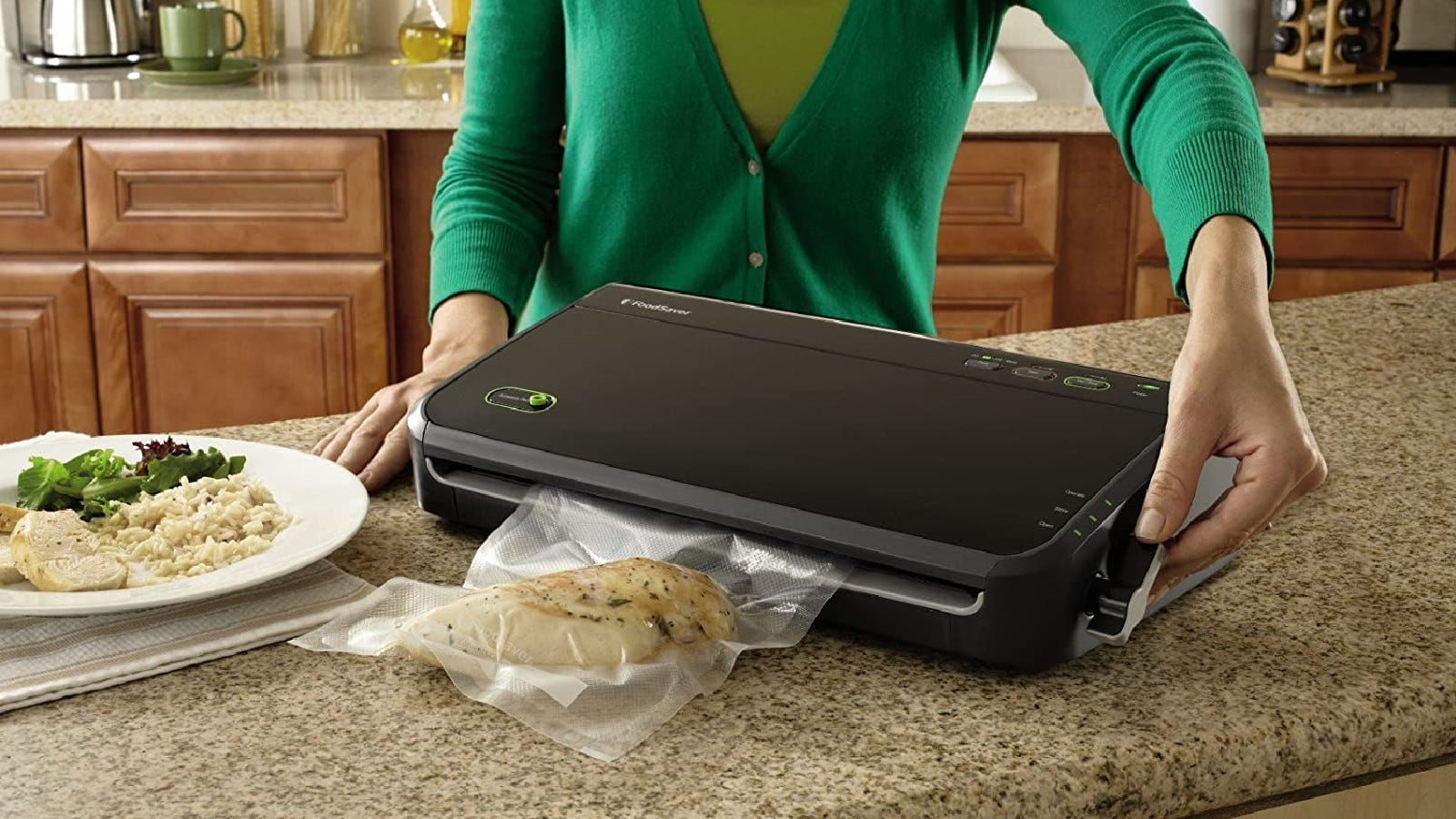 A woman sealing a chicken breast using her new FoodSaver.