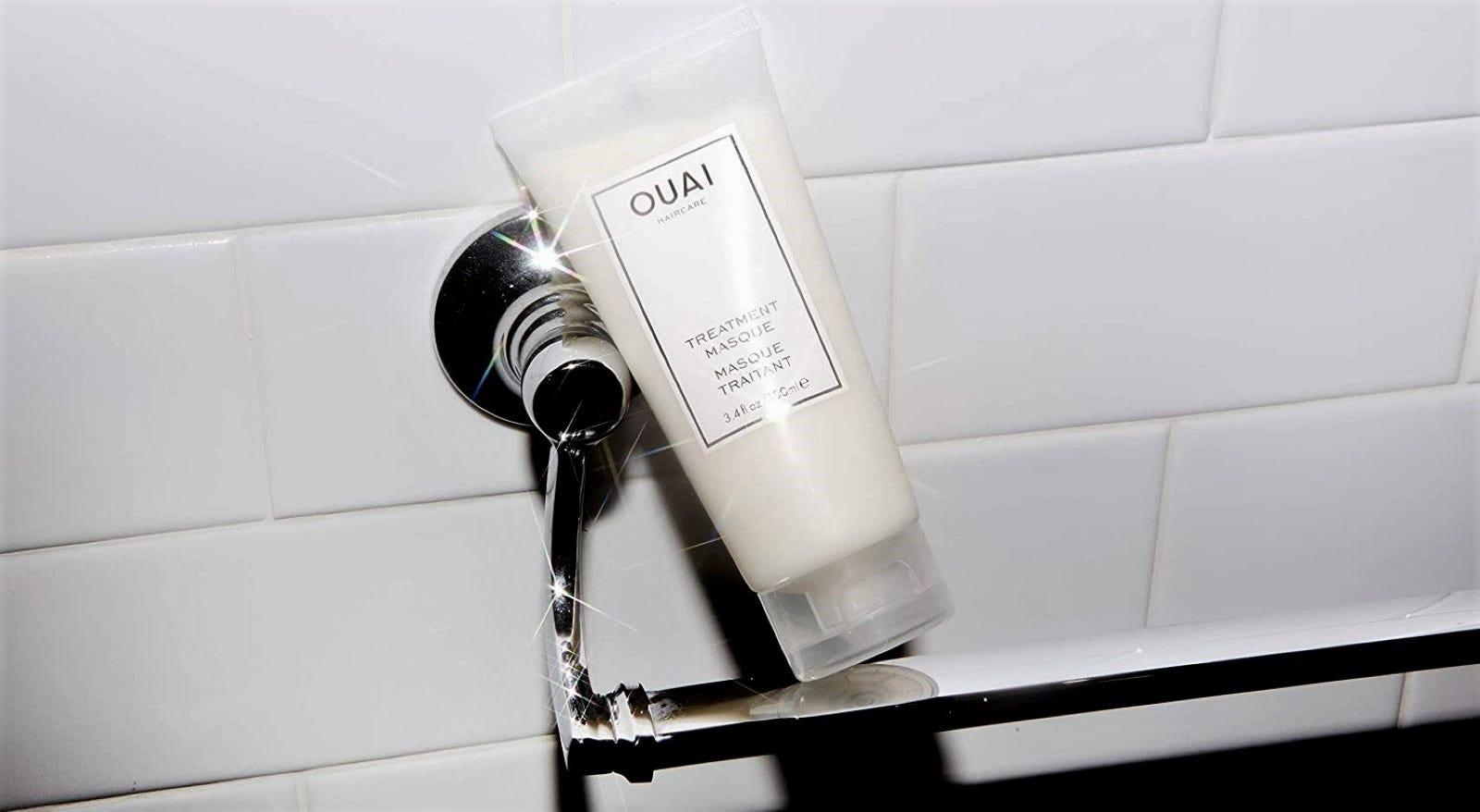 A tube of OUAI Treatment Mask sitting on a towel rack in a bathroom.