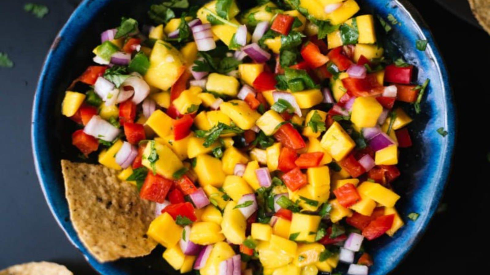 A bowl of fresh mango salsa using ingredients like mango, bell pepper, onion and cilantro.
