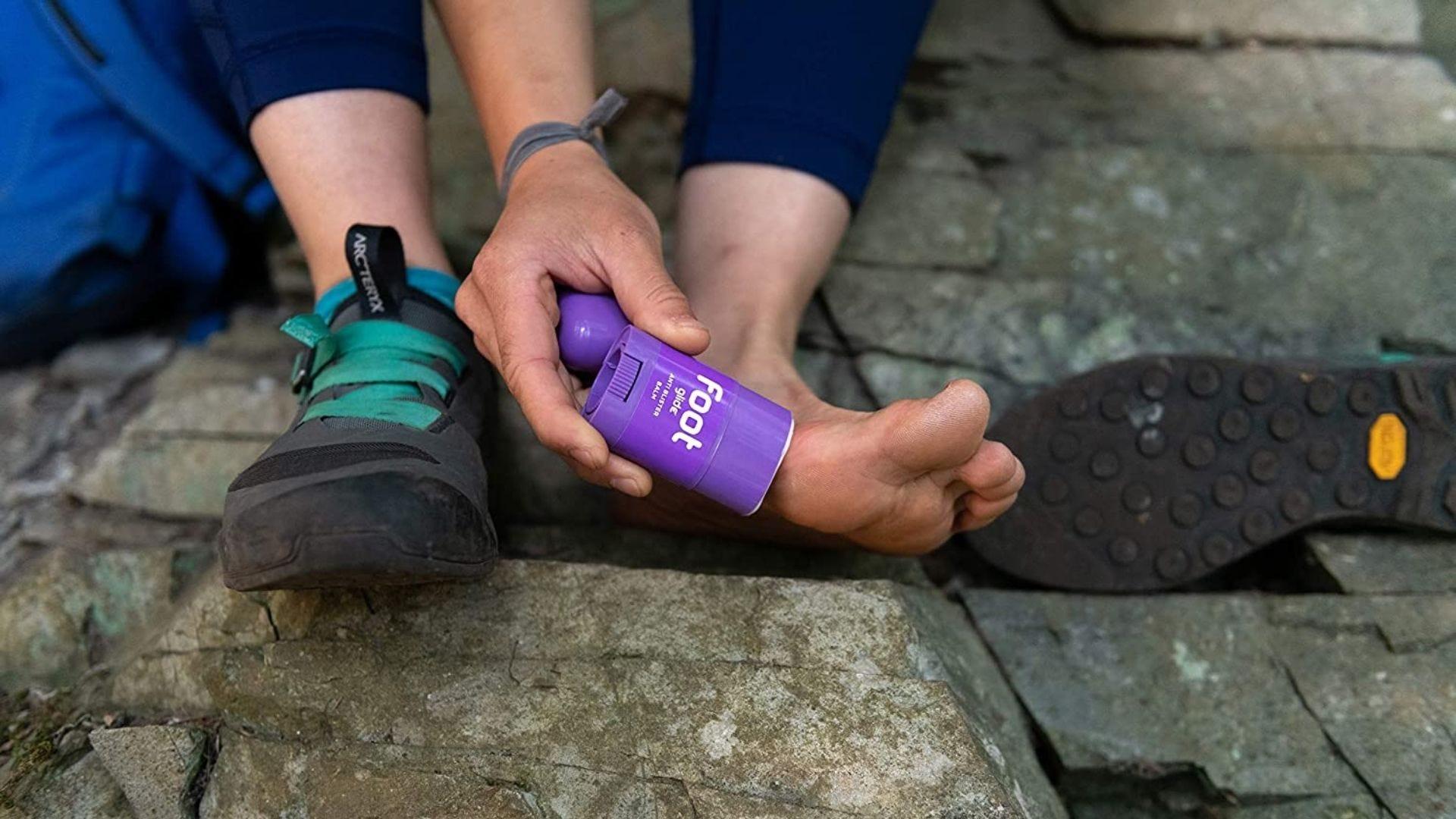 Someone rubs a purple balm stick onto their foot