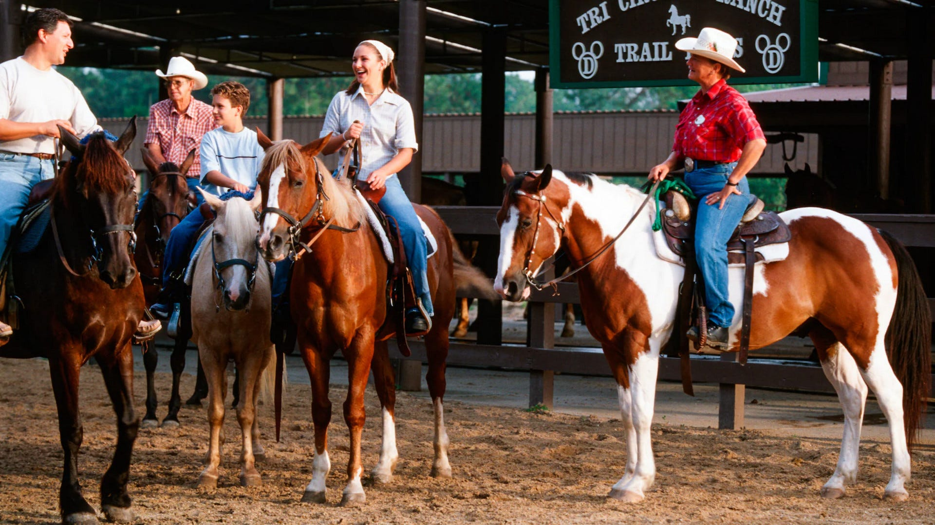 A cast member and family saddle up to ride at the Tri-Circle D Ranch at Disney World.
