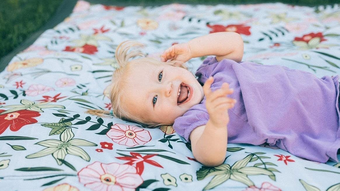 A toddler laying on a beach blanket.
