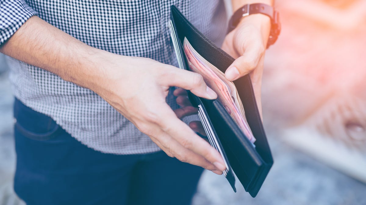man holds his wallet with cash in the middle pocket