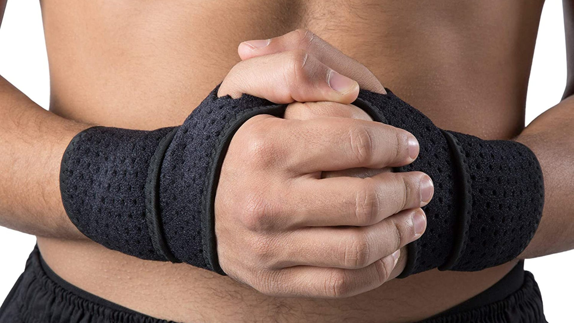 A close up of a man's hands clasped together in front of his torso while wearing a black wrist brace on both hands.