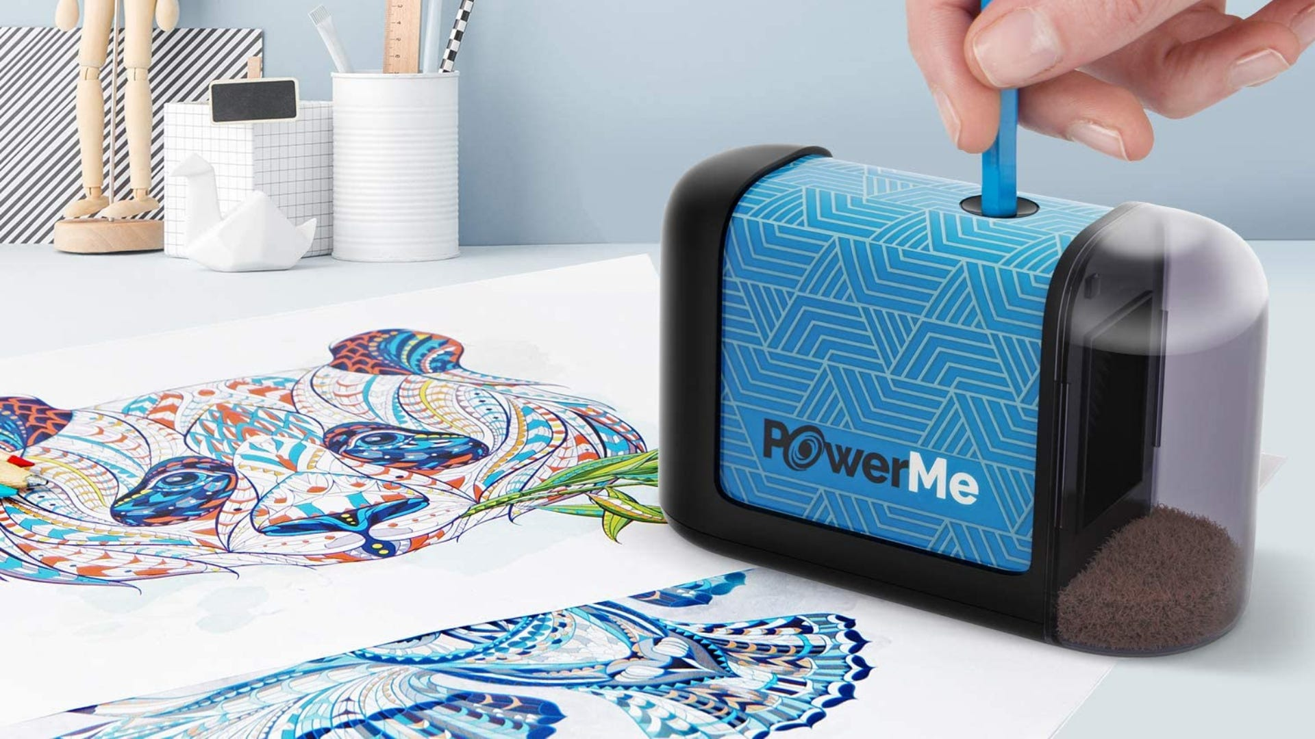 A person place a blue pencil into a blue and black patterned electric pencil sharpener that is sitting on a colorful drawing of a panda.