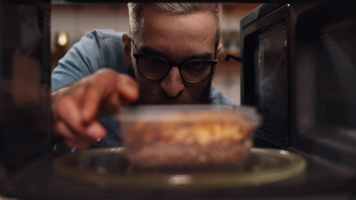 A man putting a container of leftover food in a microwave.