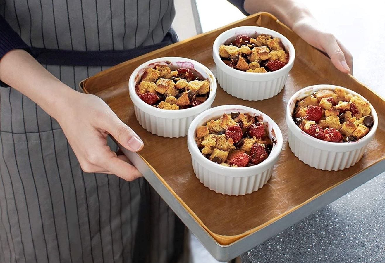 Four ramekins on a tray with cereal in them.