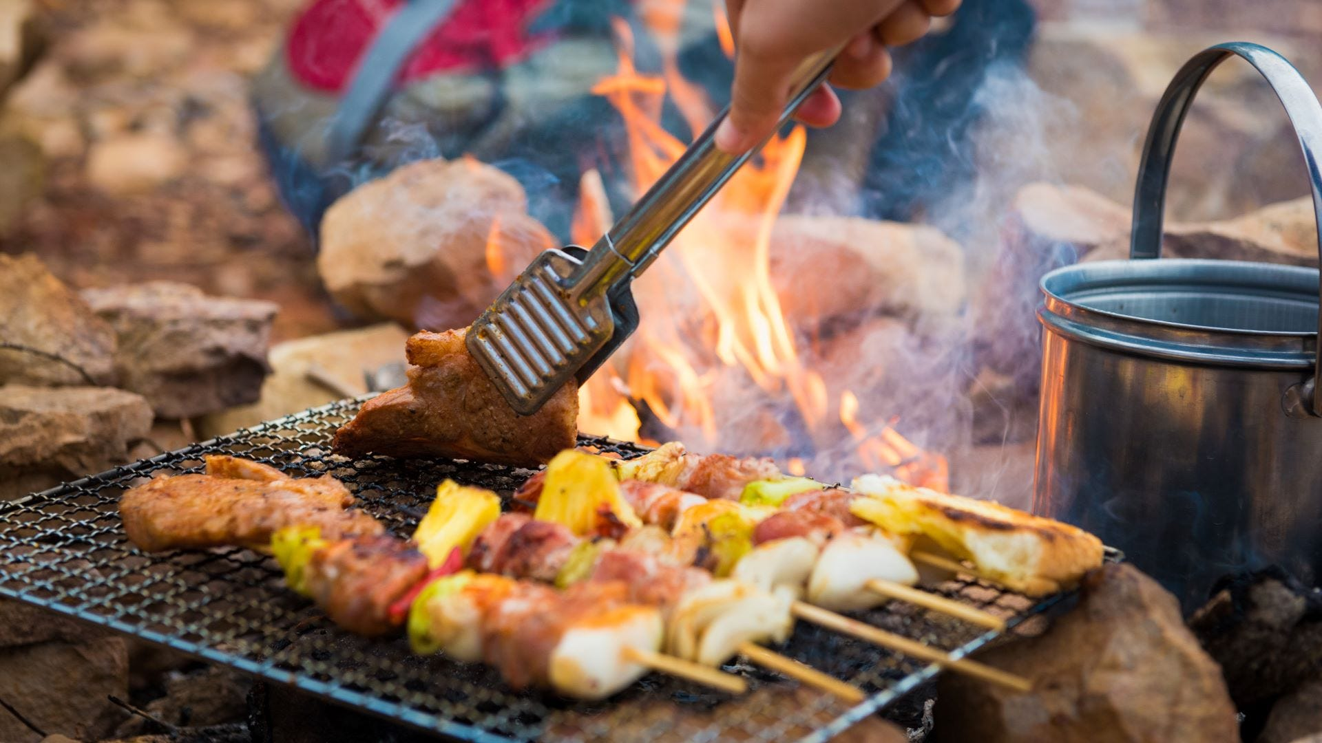 Someone using tongs to flip meat over on a campfire grill loaded with food.