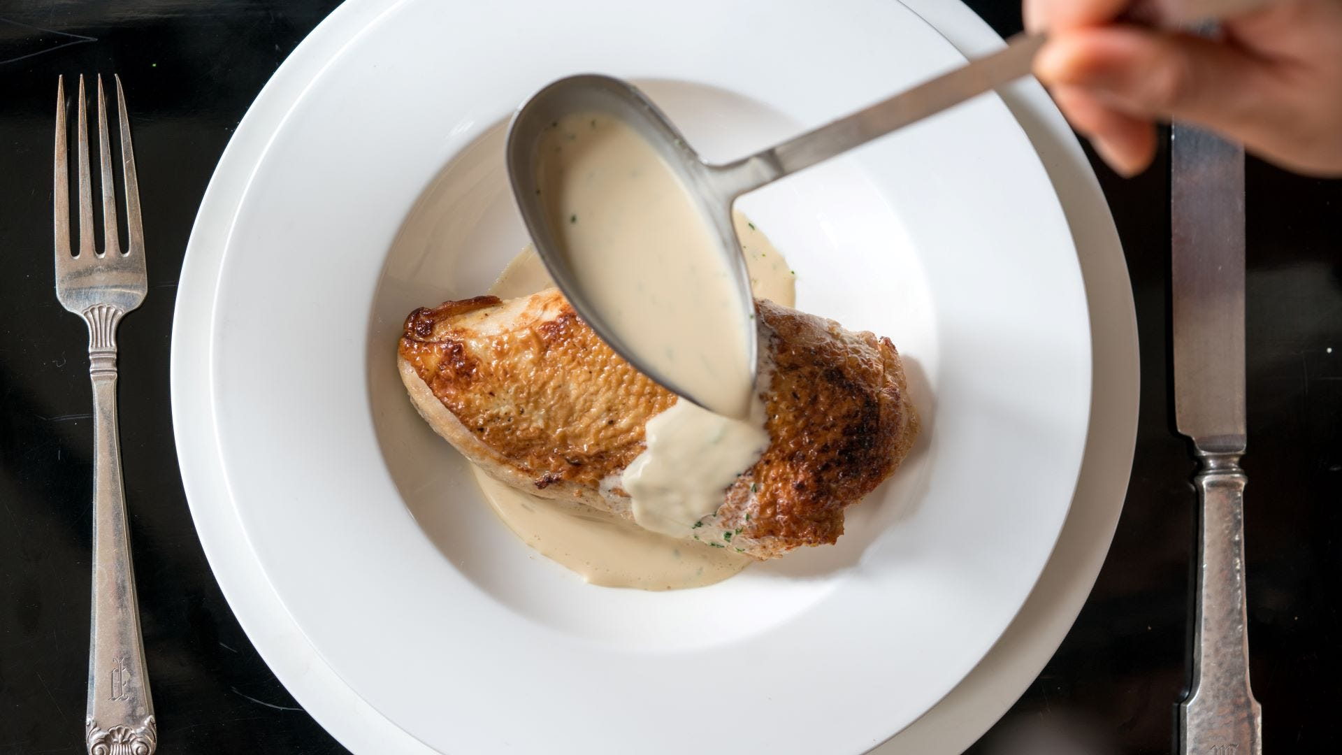 Someone ladling a veloute sauce over a chicken breast.