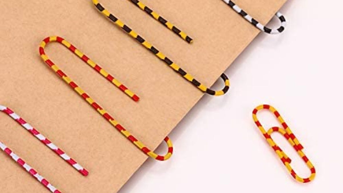 Striped paper clips on brown paper.