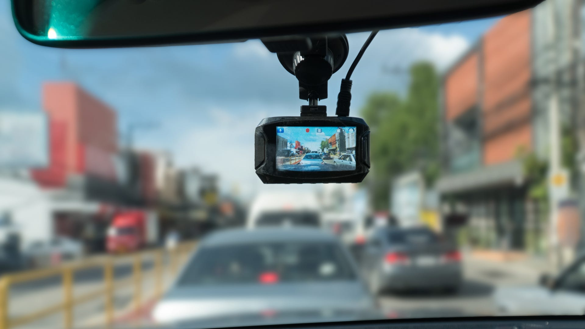 A dash camera that's attached to the rearview mirror records the cars in front of it.