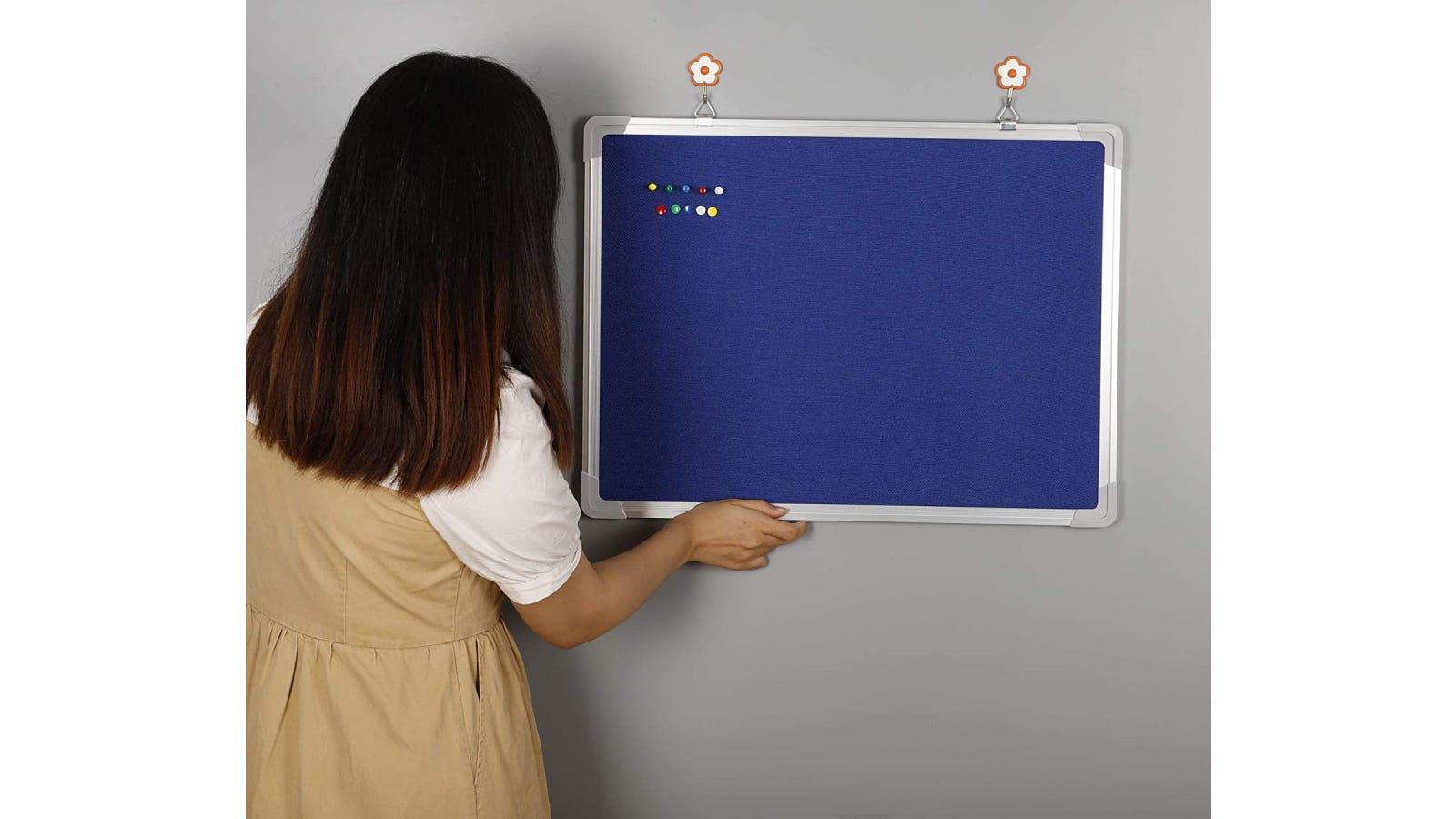 A woman hanging a blue felt bulletin board.