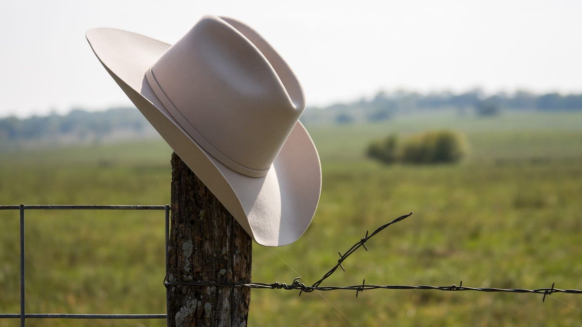 a cowboy hat resting on a wooden fence post in the country