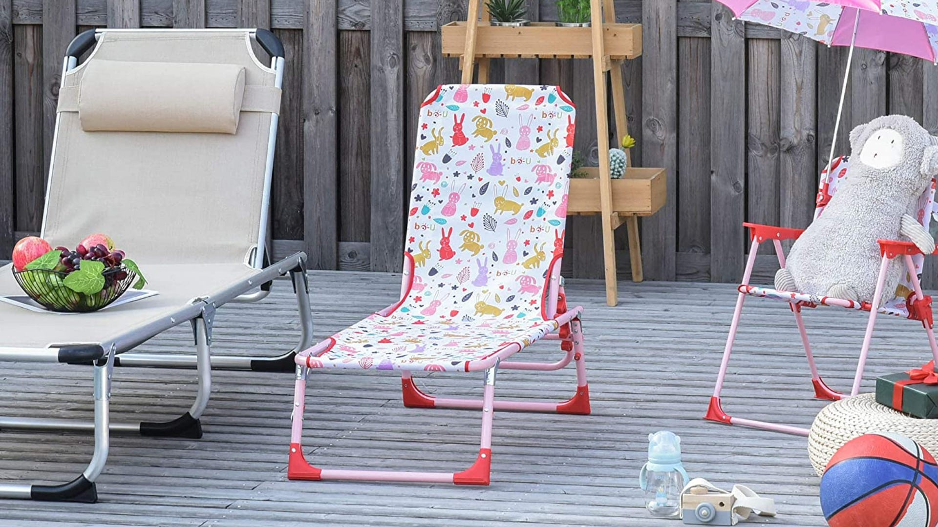 A colorful child's chaise lounge chair sitting next to toys on a deck.