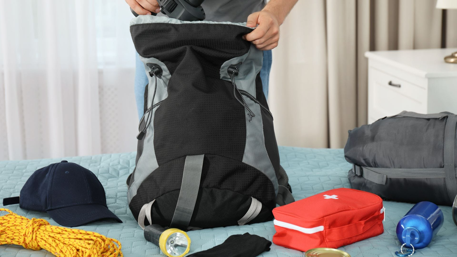 A man packing a hiking backpack on a bed with supplies surrounding it.