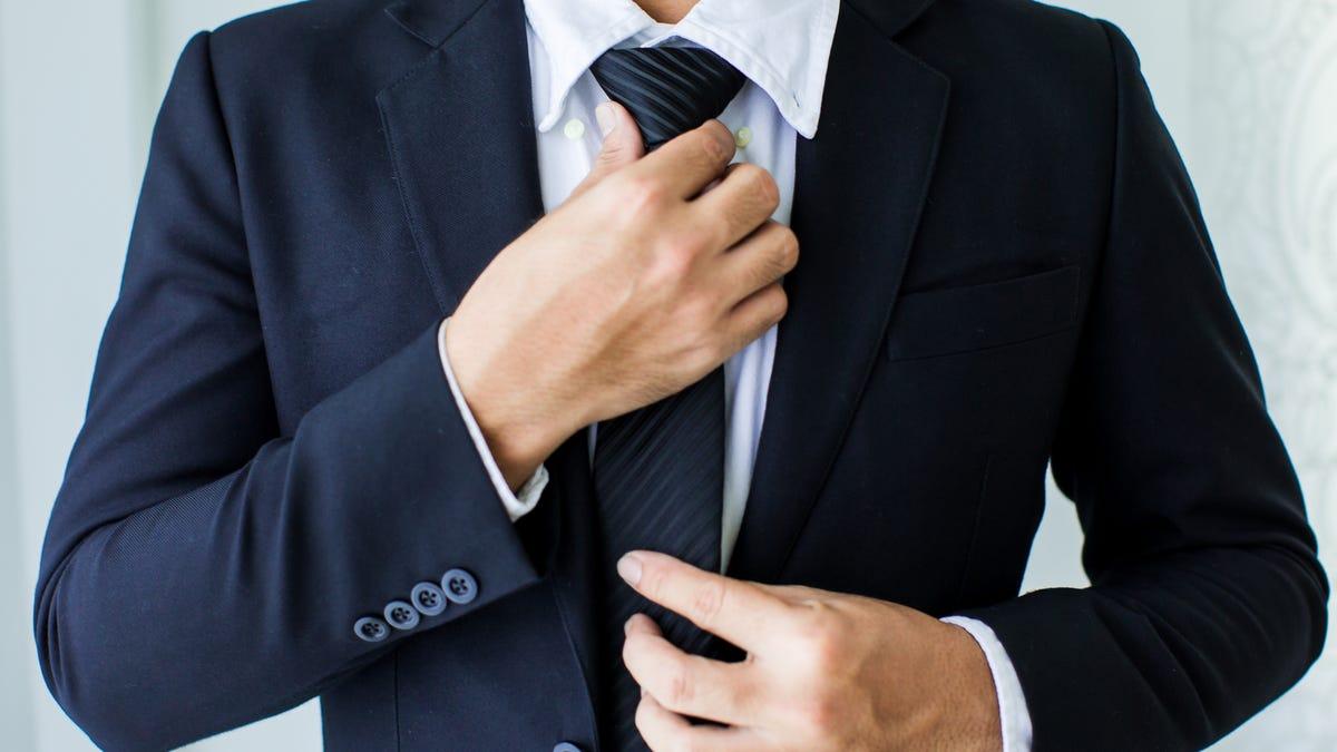 a man in a suit adjusting his necktie