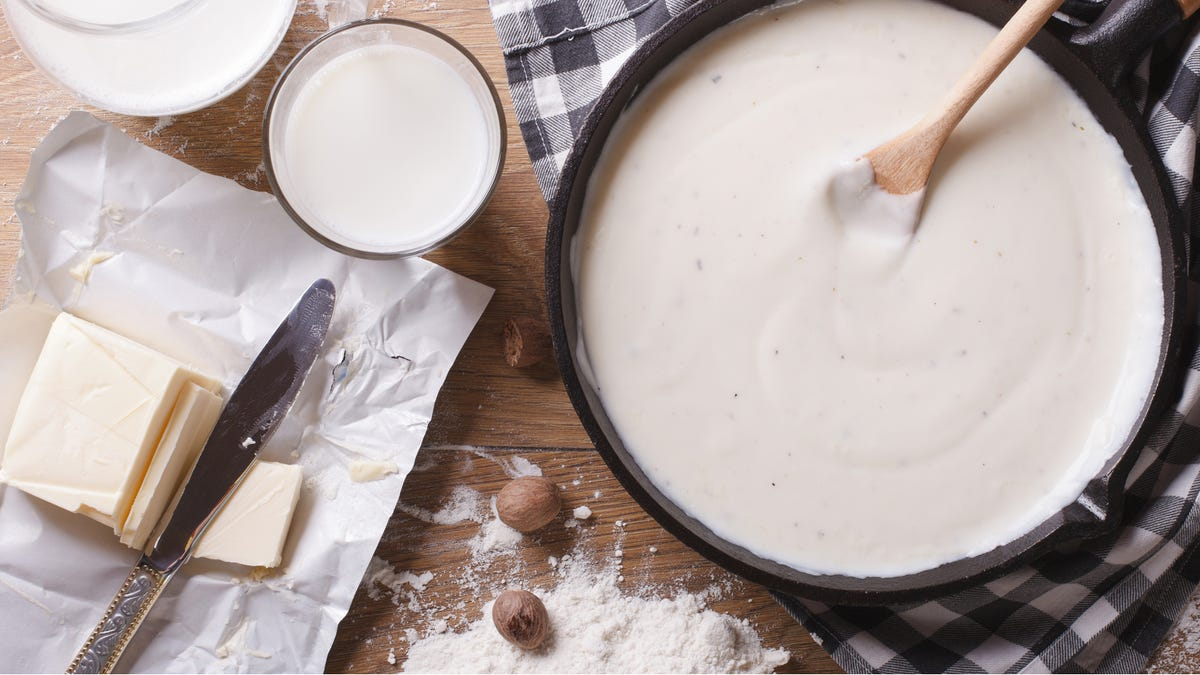 An image of ingredients used to make a rich bechamel sauce, with a deep skillet filled with freshly made sauce.