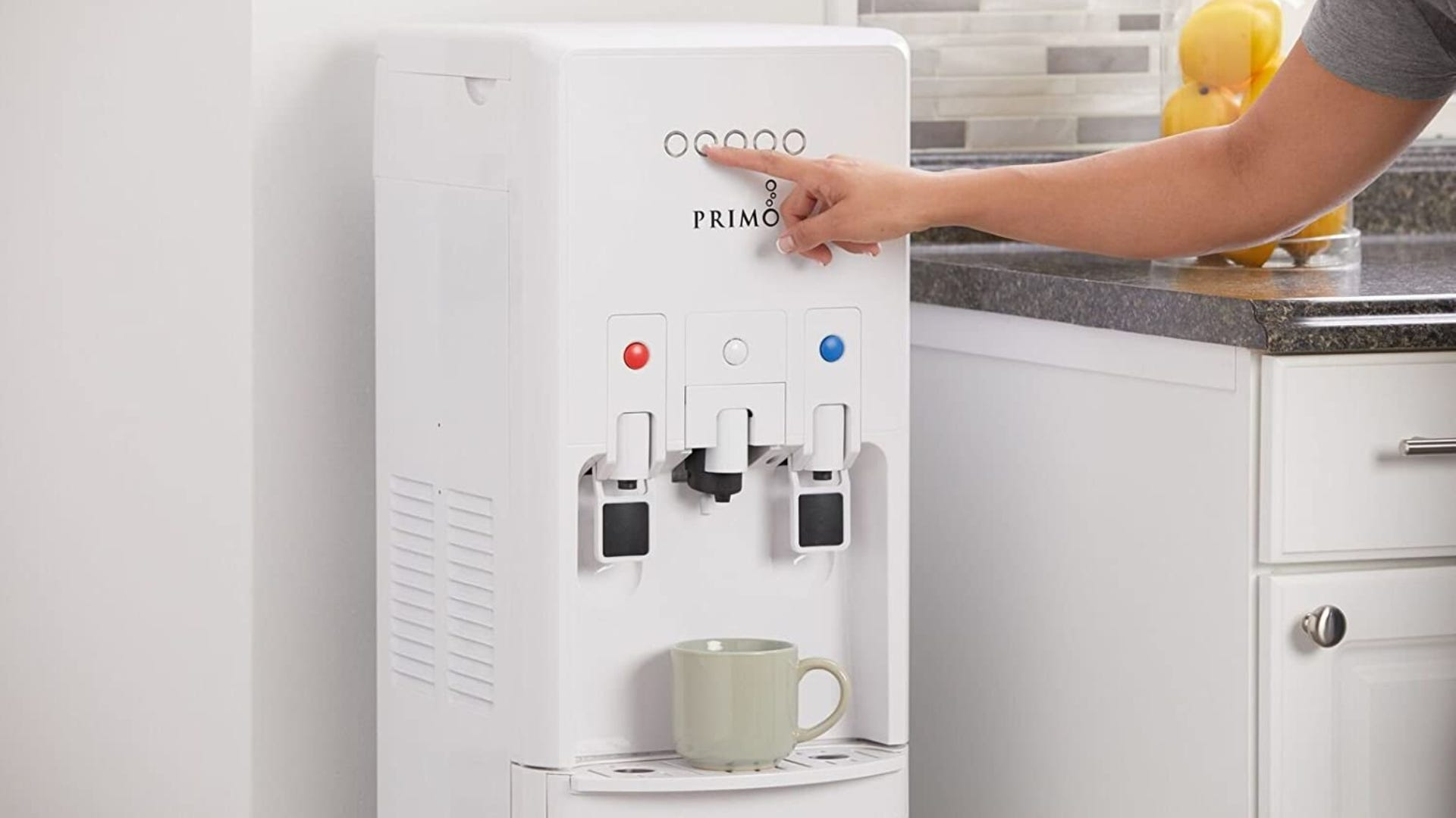 A person pushing a button on a white water cooler to dispense liquid into a mug.