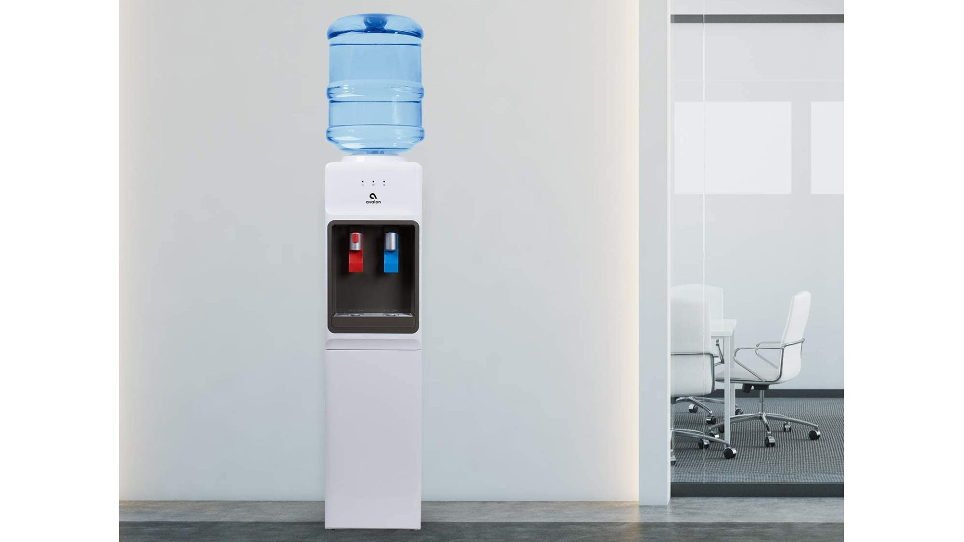 A whit water cooler with a blue jug sitting in an office.