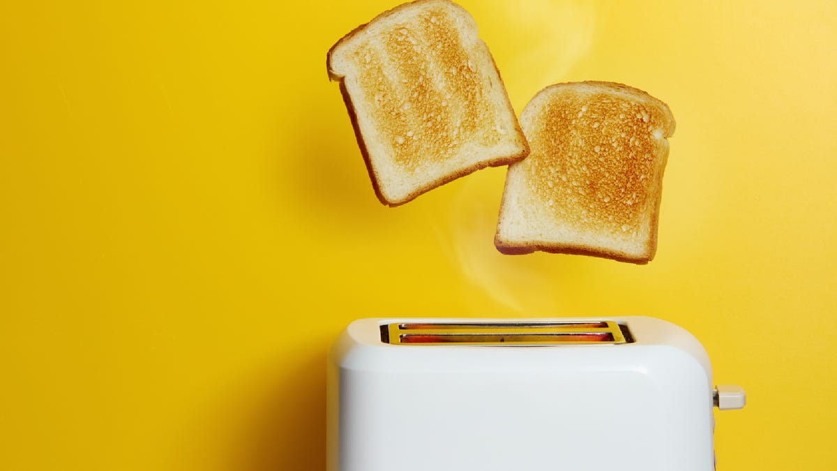 Slices of toast jumping out of the toaster against yellow background.